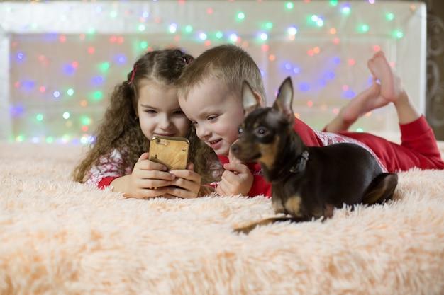 Kinder spielen mit dem telefon im schlafanzug in der nähe eines hundes
