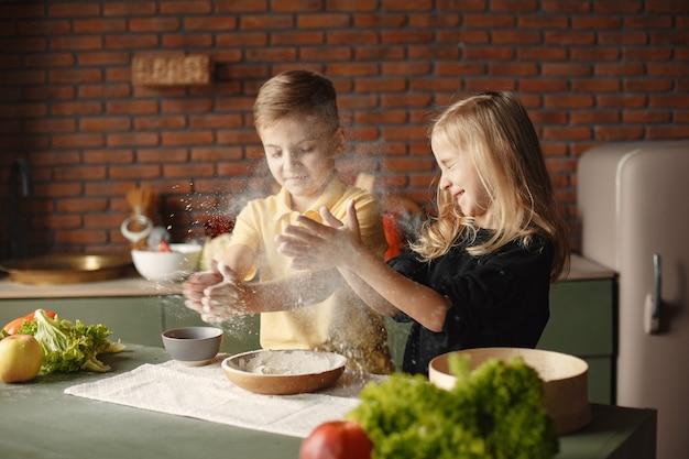 Kinder spielen mit einem mehl in einer küche