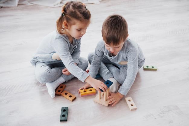 Kinder spielen mit einem spielzeugdesigner auf dem boden des kinderzimmers. zwei kinder, die mit bunten blöcken spielen. kindergarten-lernspiele