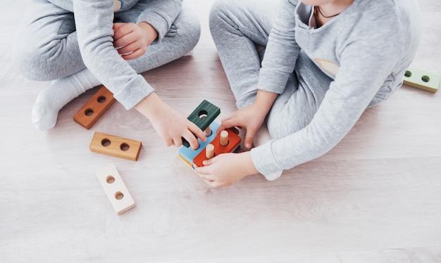 Kinder spielen mit einem spielzeugdesigner auf dem boden des kinderzimmers. zwei kinder spielen mit bunten blöcken. kindergarten-lernspiele