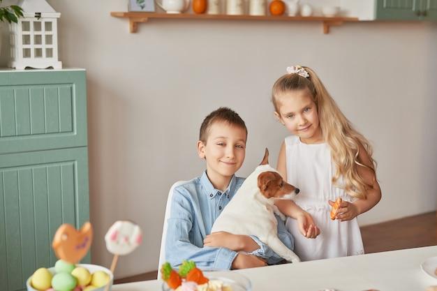 Kinder spielen mit ihrem hund auf einem mit ostern geschmückten tisch