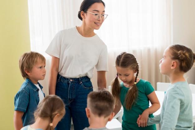 Kinder spielen mit ihrem lehrer