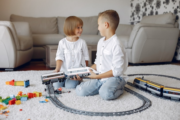 Kinder spielen mit lego und spielzeugeisenbahn in einem spielzimmer