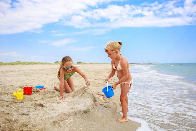 Kinder spielen mit sand am strand.