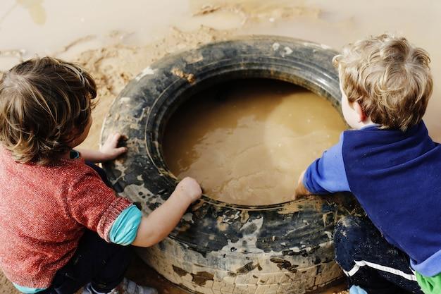 Kinder spielen mit schlamm und schmutzigem wasser