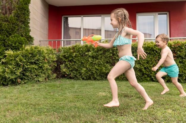 Kinder spielen mit wasserpistolen am pool
