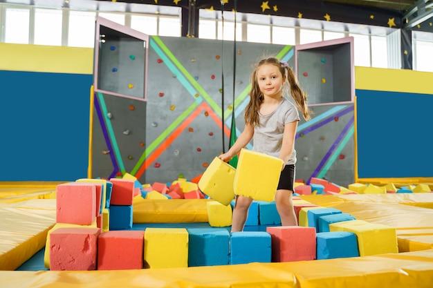Kinder spielen mit weichen würfeln im trockenen pool im spielzentrum. spielplatz mit schaumstoffblöcken im trampolinclub