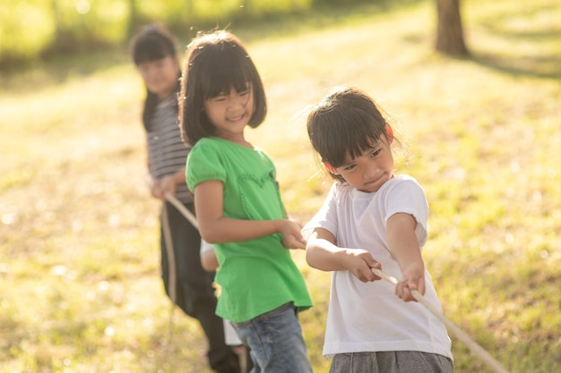 Kinder spielen tauziehen im park auf sunsut