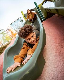Kinder spielen zusammen auf einer rutsche