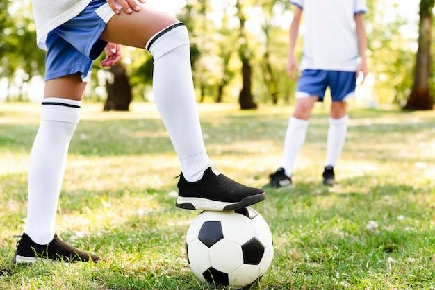 Kinder spielen zusammen fußball im freien