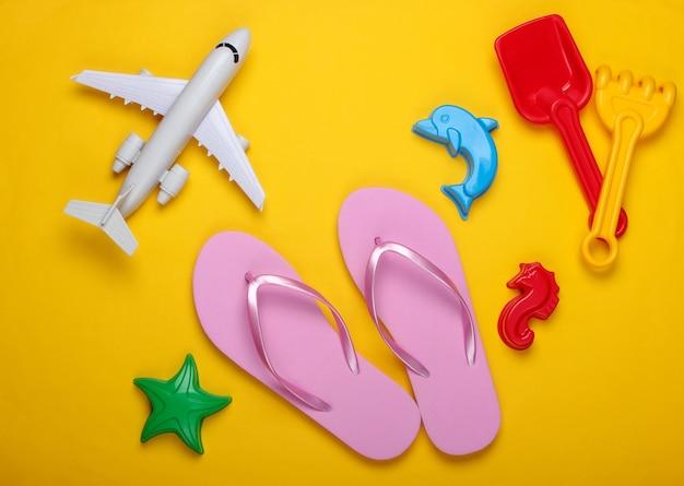 Kinder strandspielzeug, flip flops, flugzeug auf einem gelben