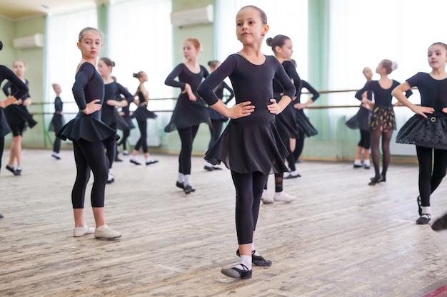 Kinder tanzen mit einem trainer in einem großen trainingsraum.