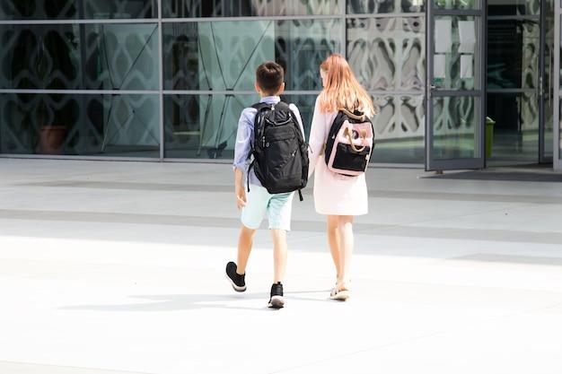 Kinder teenager schulkinder jungen und mädchen auf dem hintergrund der betonwand mit rucksäcken, die...