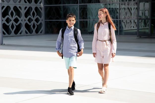 Kinder teenager schulkinder jungen und mädchen auf dem hintergrund der betonwand mit rucksäcken gehen ar...