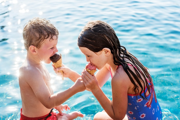 Kinder teilen eis am pool