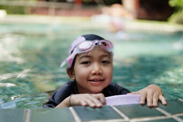 Kinder üben das schwimmen im pool.