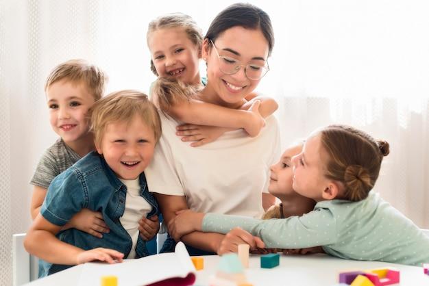 Kinder umarmen ihren lehrer