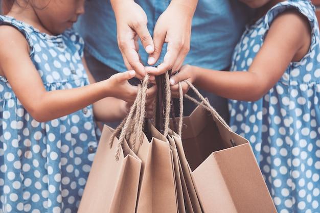 Kinder und eltern helfen, einkaufstaschen auf dem im einkaufszentrum zu halten