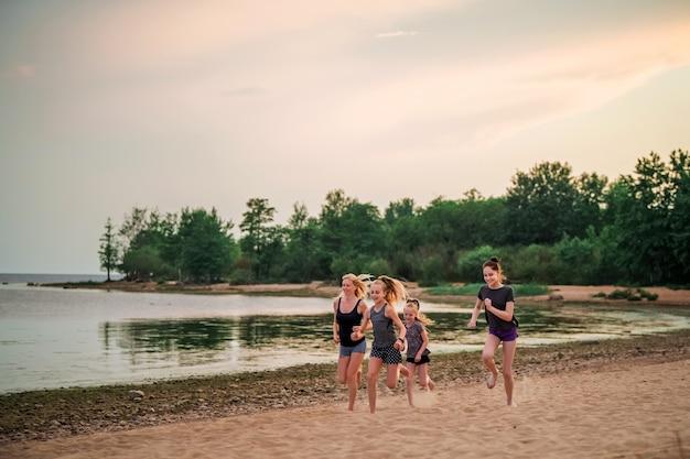 Kinder und erwachsene mädchen laufen entlang der küste in sportbekleidung auf einem hintergrund der natur bei sonnenuntergang