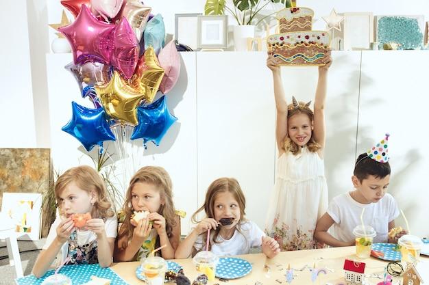 Kinder- und geburtstagsdekorationen. jungen und mädchen am tisch mit essen, kuchen, getränken und party-gadgets.