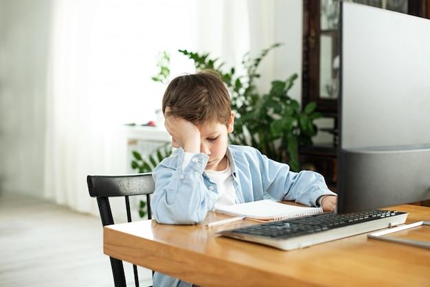 Kinder und geräte. fernunterricht während der isolation während der quarantäne. trauriger und verärgerter junge mit laptop zu hause. lebensstil. lockdown und soziale distanzierung