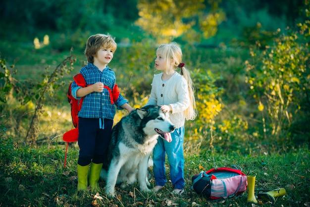 Kinder und hund auf naturhintergrund kinder, die mit haustierhund campen