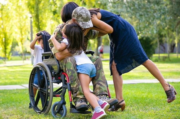 Kinder und ihre mutter umarmen den behinderten militärvater im ruhestand im park. veteran des krieges oder rückkehr nach hause konzept