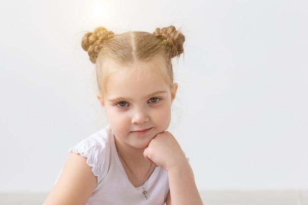 Kinder- und kinderkonzept kleines kindermädchen im weißen hemd, das auf dem boden sitzt mit