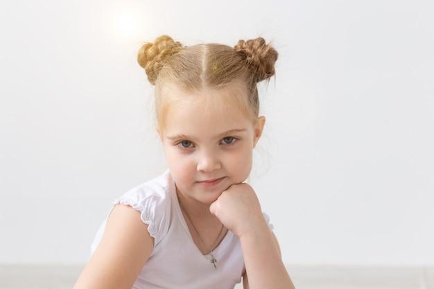 Kinder- und kinderkonzeptporträt des schönen kleinen kindermädchens, das ihr kinn auf der hand hält und