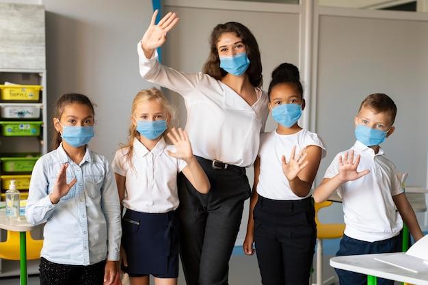 Kinder und lehrer posieren beim tragen einer medizinischen maske