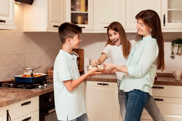 Kinder und mutter bereiten essen in der küche zu