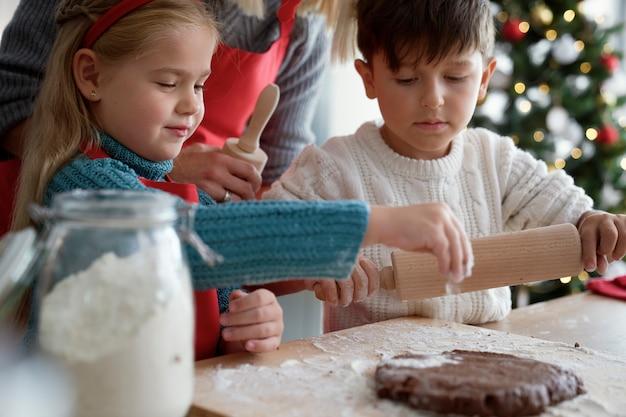 Kinder und mutter bereiten teig für lebkuchenplätzchen vor