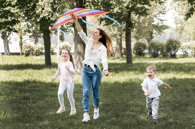 Kinder und mutter spielen mit buntem drachen