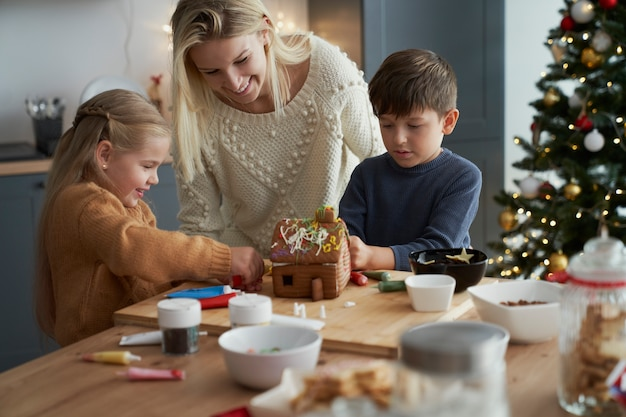 Kinder und mutter verzieren lebkuchenhaus in der küche
