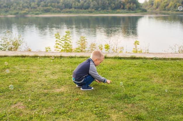 Kinder- und naturkonzept - junge, der versucht, seifenblasen zu fangen