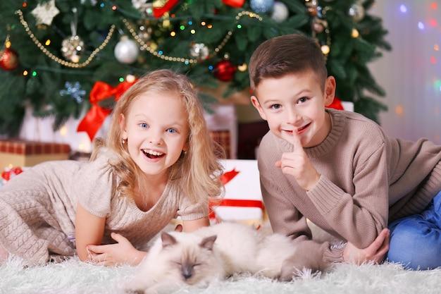 Kinder und schlafende katze im geschmückten weihnachtszimmer