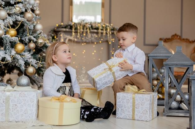 Kinder unter weihnachtsbaum mit geschenkboxen. dekoriertes wohnzimmer mit traditionellem kamin