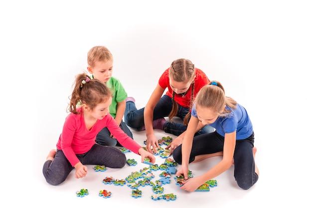 Kinder unterschiedlichen alters lösen gemeinsam das puzzle. teamwork, zusammenarbeiten, problemkonzept lösen