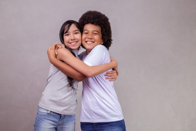 Kinder unterschiedlicher vielfalt auf grauem hintergrund. japanisches mädchen mit einem afro-kind auf grauem hintergrund mit platz für text.