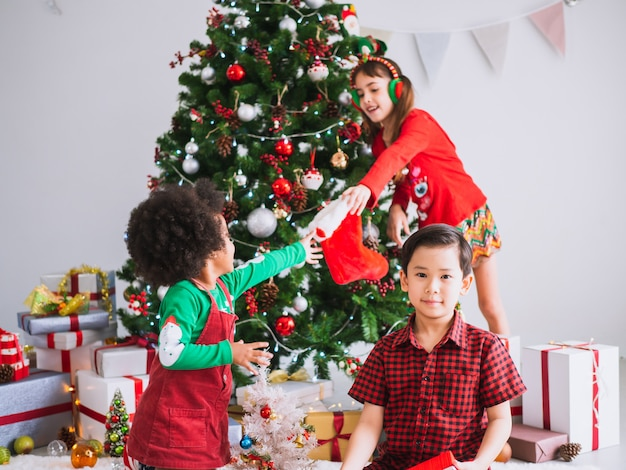 Kinder vieler nationalitäten feiern weihnachtstag, kinder unter weihnachtsbaum mit geschenkboxen