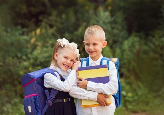 Kinder von 7 bis 8 jahren, grundschüler mit rucksäcken und schuluniformen, lächelnd