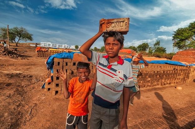 Kinder von arbeitern, die helfen, traditionelle ziegelsteine von hand im ziegelofen oder in der fabrik herzustellen.