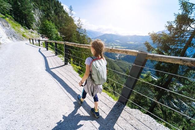 Kinder wandern am sommertag in den alpenbergen österreichs, ruhen sich auf felsen aus und bewundern die atemberaubende aussicht auf berggipfel. aktiver familienurlaub mit kindern.
