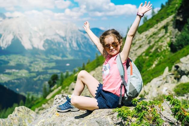 Kinder wandern an schönen sommertagen in den alpenbergen österreichs, ruhen sich auf felsen aus und bewundern die atemberaubende aussicht auf berggipfel.