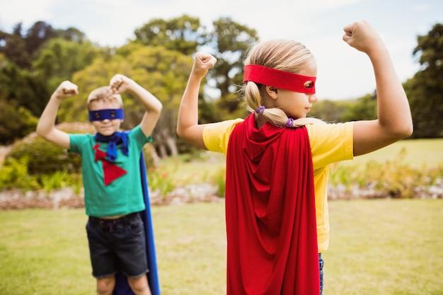 Kinder, welche die superheldkostümaufstellung tragen