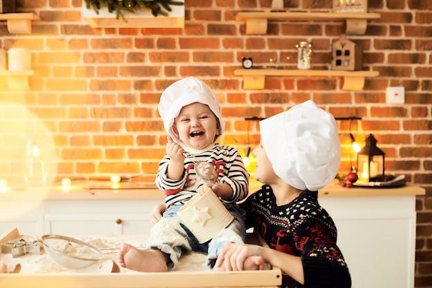 Kinder werden gekocht und mit mehl und teig in der küche gespielt