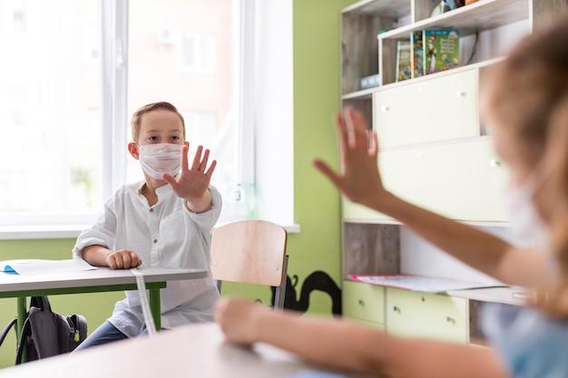 Kinder winken im klassenzimmer und halten dabei soziale distanz