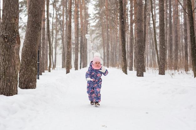 Kinder-, winter- und naturkonzept - nahaufnahme des entzückenden kindes, das mit schnee im park spielt