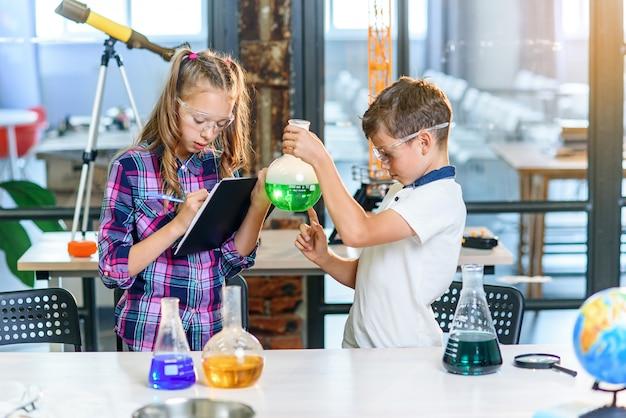 Kinder zeichnen die ergebnisse der experimente im notizbuch auf. zwei junge kluge kaukasische schüler in schutzgläsern experimentieren mit grüner flüssigkeit in becherglas und trockeneis.