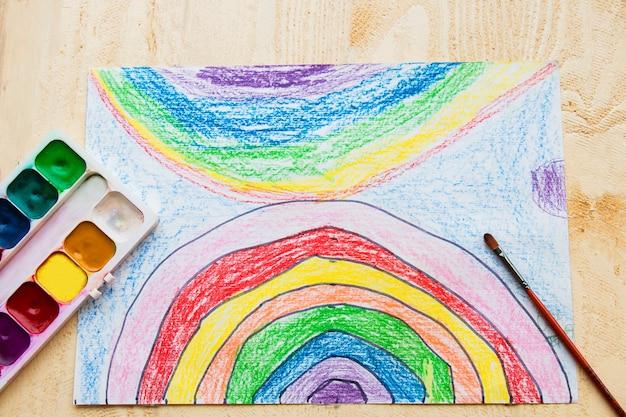 Kinder zeichnen einen regenbogen in den himmel